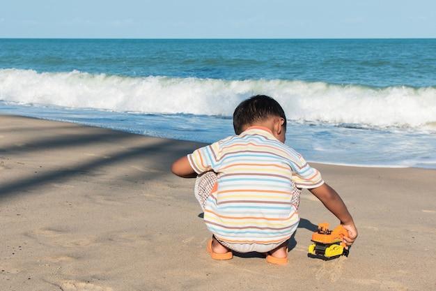 Nettes spielzeugspielzeugauto des kleinen jungen auf dem strand