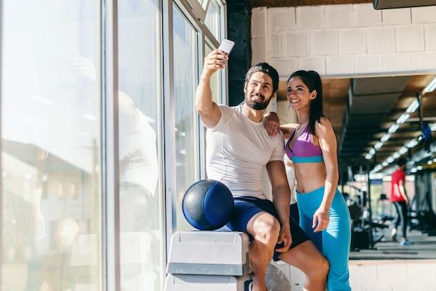 Nettes sportliches paar, das selfie mit smartphone im fitnessstudio nimmt.