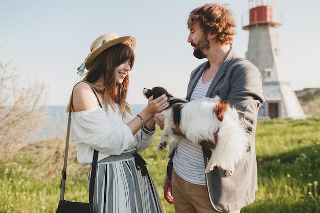 Nettes stilvolles hipster-paar in der liebe, die mit hund in der landschaft geht