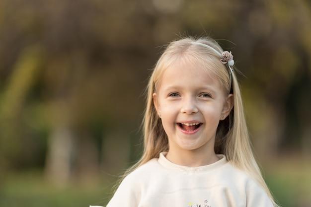 Nettes stilvolles kleines mädchen mit langen blonden haaren, die im herbstpark gehen