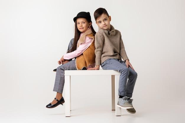 Nettes stilvolles kleines paarkindmädchen und -junge in modischen kleidern, die zusammen im studio sitzen