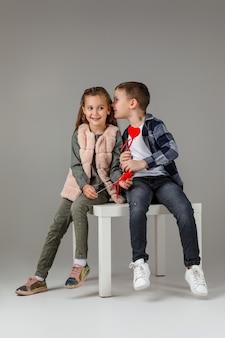 Nettes stilvolles kleines paarkindmädchen und -junge mit roten herzen auf stock in modischen kleidern, die zusammen sitzen