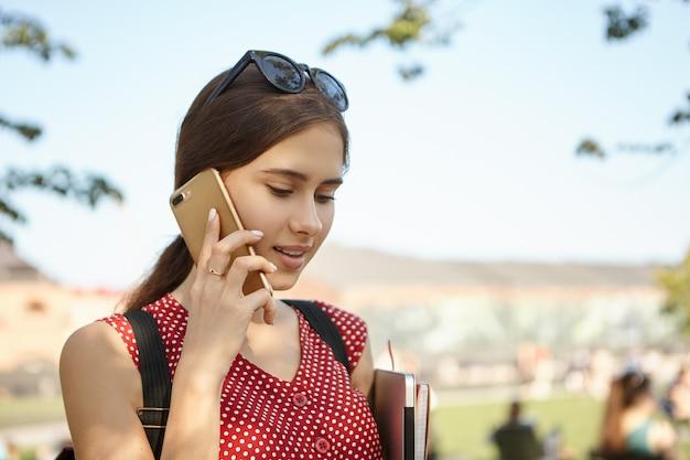 Nettes stilvolles studentenmädchen, das rucksack und schwarze schatten trägt, die draußen mit handy an ihrem ohr aufwerfen, telefongespräch führen, mit freund sprechen. bildungs-, technologie- und kommunikationskonzept