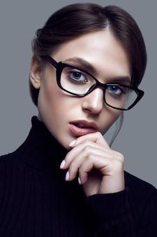 Nettes studentenmädchen, das schwarzen rollkragenpullover und stilvolle brillen trägt