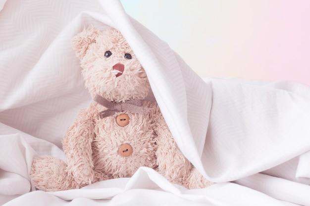 Nettes teddybärspielverstecken mit gewebe, glückliches gefühlkonzept.