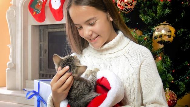 Nettes teenager-mädchen, das graues kätzchen unter dem weihnachtsbaum streichelt