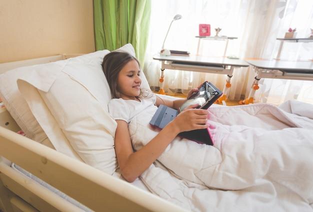 Nettes teenager-mädchen, das morgens im bett liegt und digitales tablet benutzt