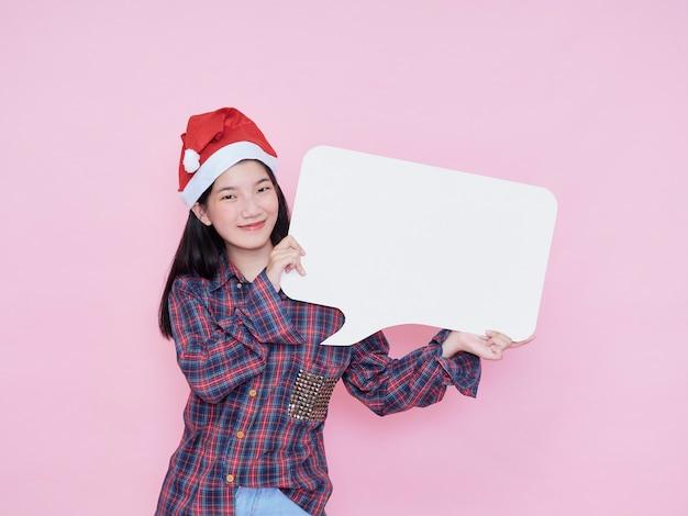 Nettes teenager-mädchen in der weihnachtsmütze, die finger auf leerem plakat zeigt, während auf rosa hintergrund steht.