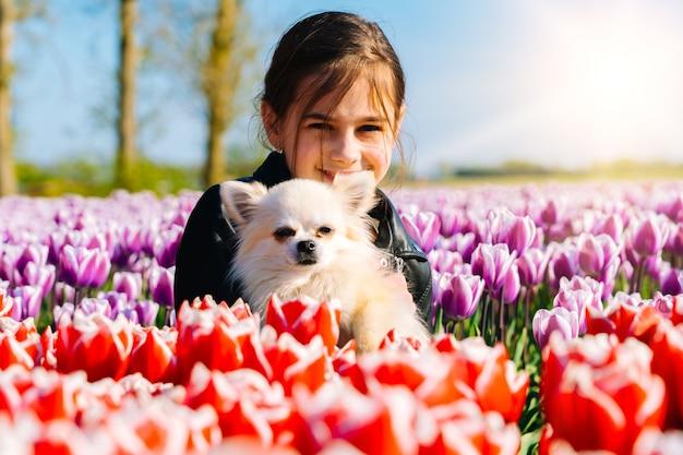 Nettes teenager-mädchen mit langem haar, das tulpenblume auf tulpenfeldern in der region amsterdam, holland, niederlande riecht. magische niederländische landschaft mit tulpenfeld in holland trevel und frühlingskonzept.