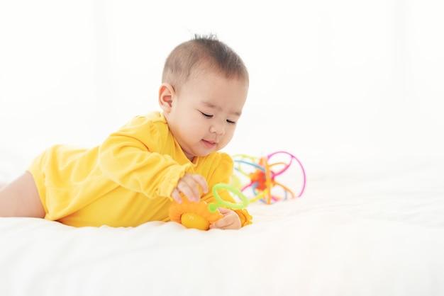 Nettes thailändisches neugeborenes, das lustig im bett spielt. kleines baby in der windel, die auf seinem bauch auf weißem bett mit spielzeug liegt