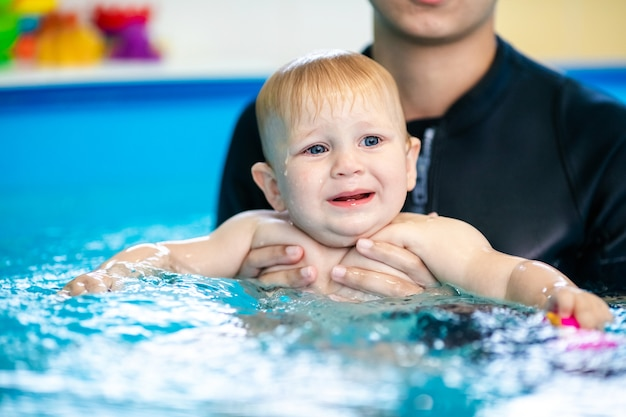 Nettes trauriges baby, das lernt, im speziellen pool für kleine kinder zu schwimmen