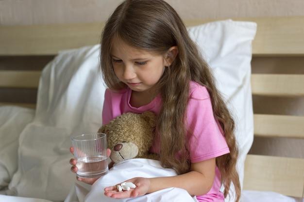 Nettes trauriges krankes kleines mädchen sitzt auf dem bett und hält ein glas wasserpillenmedizin und teddybär