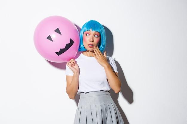 Nettes und dummes asiatisches mädchen in der blauen perücke, das halloween feiert und überrascht auf ballon mit gruseligem gesicht schaut.
