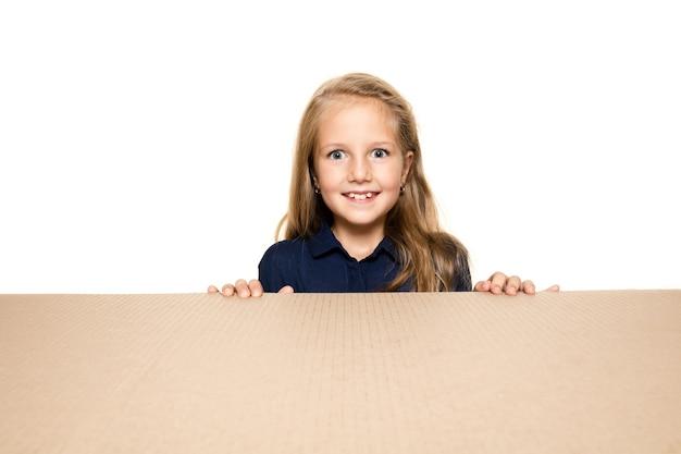 Nettes und erstauntes kleines mädchen, das das größte postpaket öffnet. aufgeregtes junges weibliches modell oben auf dem karton, der nach innen schaut.