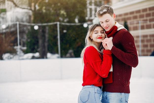 Nettes und liebevolles couplein rote strickjacken in einer winterstadt