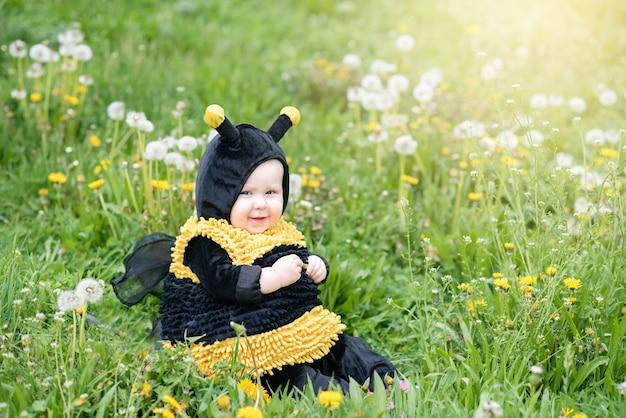 Nettes und nettes porträt des kleinen kindes sitzend in blühenden blumen des löwenzahns im gelben bienenkostüm.