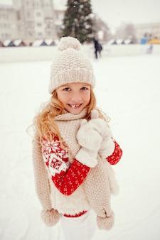 Nettes und schönes kleines mädchen in einer winterstadt