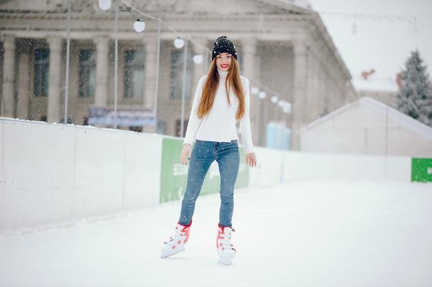 Nettes und schönes mädchen in einer weißen strickjacke in einer winterstadt