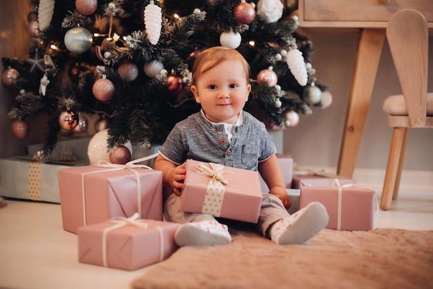 Nettes unschuldiges baby mit weihnachtsgeschenken. weihnachtsgeschenke