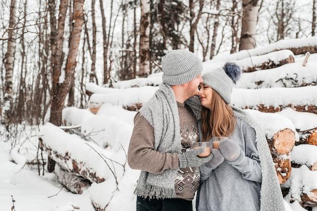 Nettes verliebtes paar, das auf dem baumstamm, winterwald sitzt. kunstwerk.