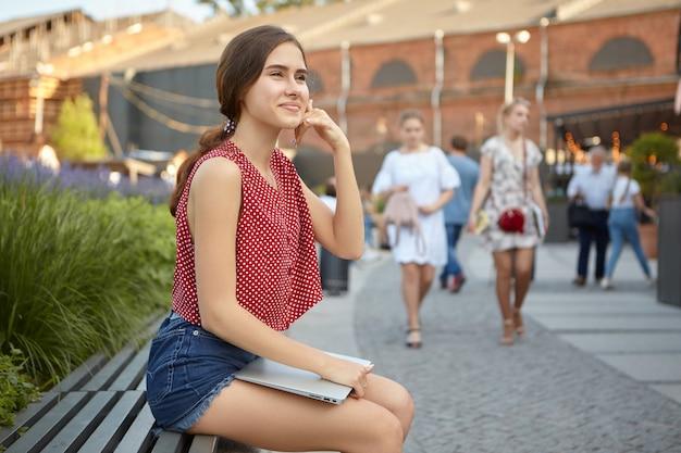Nettes verspieltes junges mädchen gekleidet in trendigen sommerkleidern, die spaß draußen mit tragbarem computer auf schoß haben, auf bank sitzen, hand an ihrem ohr halten, als ob sie auf unsichtbarem handy sprechen