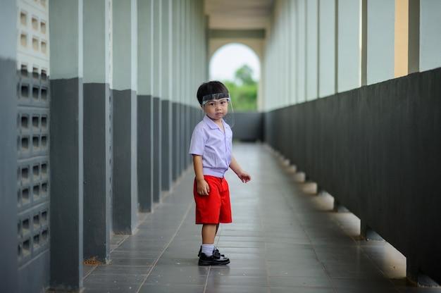 Nettes vorschulkind, das gesichtsschutz an der schule neuen normalen lebensstil an öffentlichen orten trägt.