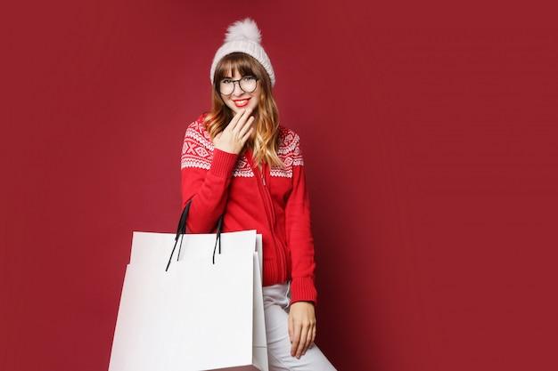 Nettes weibchen im weißen wollhut und im roten winterpullover, die mit einkaufstaschen aufwerfen