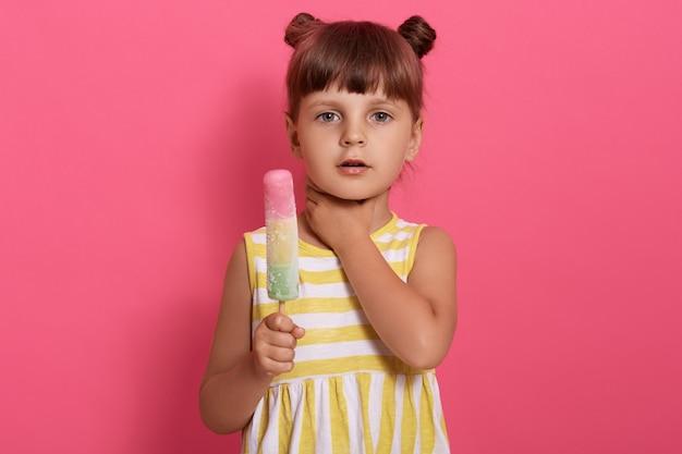 Nettes weibliches kind, das auf rosiger wand posiert, die eis hält