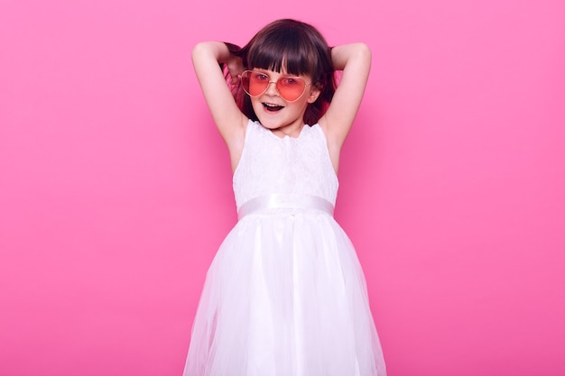 Nettes weibliches kind mit glücklichem gesichtsausdruck, der vorne mit aufregung schaut, stilvolles weißes kleid tragend, hände erhoben hält, lokalisiert über rosa wand