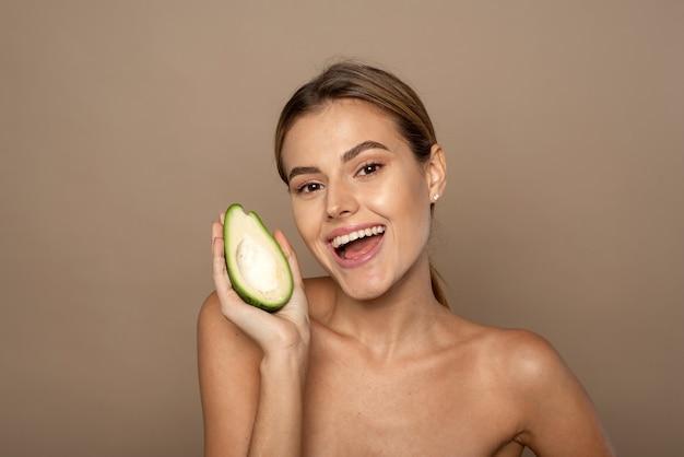 Nettes weibliches modell, das eine halbe avocado hält, lächelt und die kamera auf beigefarbenem hintergrund betrachtet.