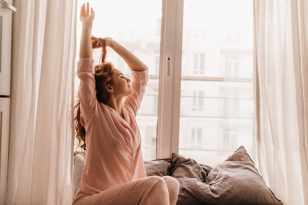 Nettes weibliches modell im rosa pyjama, das morgen genießt. angenehme ingwerfrau, die auf bett sitzt.