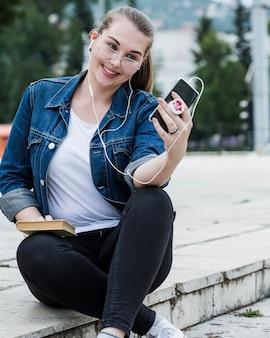 Nettes weibliches nehmendes selfie, das im park sitzt