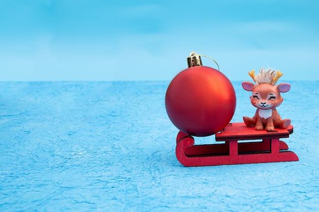 Nettes weihnachten mit rotem weihnachtsball-rentier, das auf einem schlitten sitzt.