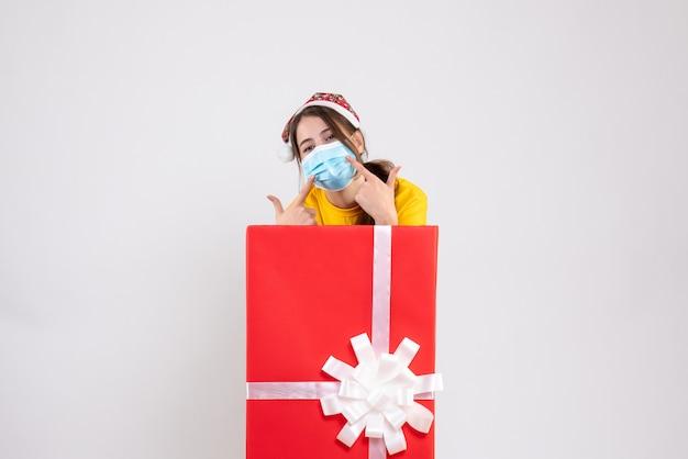 Nettes weihnachtsmädchen der vorderansicht mit weihnachtsmütze, die auf ihre maske zeigt, die hinter großem weihnachtsgeschenk steht