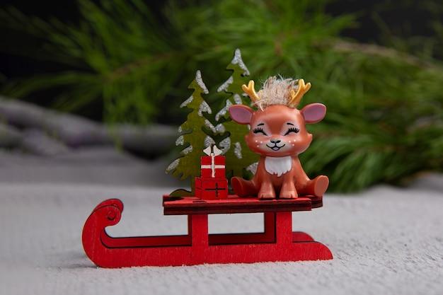 Nettes weihnachtsrentier, das auf einem schlitten-konzept der weihnachtsglücklichen neujahrspostkarte sitzt