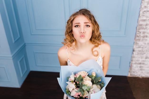 Nettes zartes blondes mädchen, das in einem studio mit blauen wänden steht und einen blumenstrauß in ihren händen hält