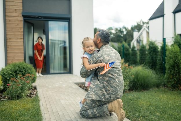 Nettes zartes mädchen. militäroffizier fühlt sich unvergesslich, als er sein süßes zartes mädchen umarmt, während er nach hause kommt
