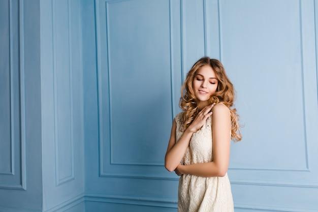 Nettes zartes schlankes mädchen mit blondem lockigem haar stehend