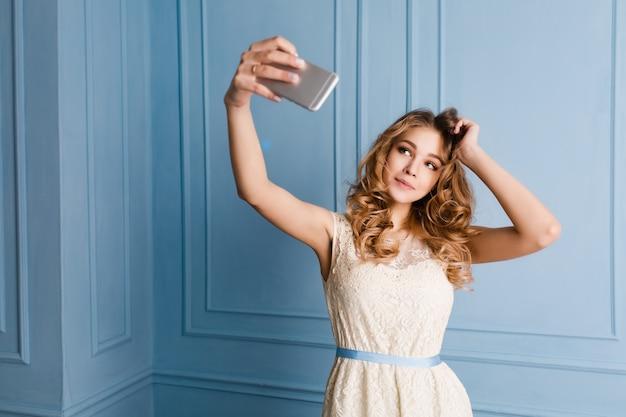 Nettes zartes schlankes mädchen mit blondem lockigem haarstand, sieht süß aus und macht ein selfie