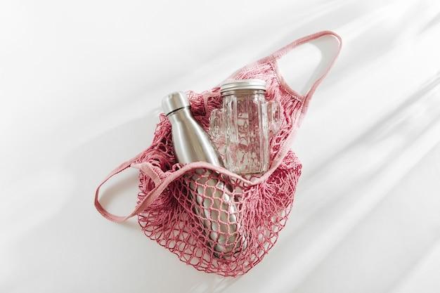 Netzbeutel aus baumwolle mit wiederverwendbarer wasserflasche aus metall, glas und strohhalm. zero-waste-konzept. umweltfreundlich