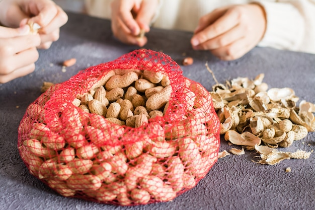 Netzbeutel mit erdnüssen in der schale und zwei mädchen im hintergrund schälen nüsse am tisch. lebensstil