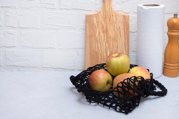 Netztasche mit äpfeln auf neutralem küchentisch mit kopierraum
