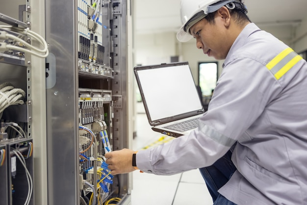 Netzwerkadministrator, der laptop in der hand hält, arbeitet konfiguration mit core-switch am rack-schrank im rechenzentrum