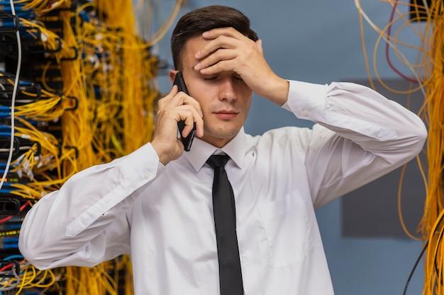 Netzwerktechniker, der am telefonmediumschuß spricht