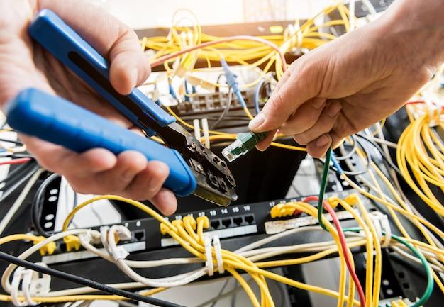 Netzwerktechniker im serverraum. anschließen von netzwerkkabeln an switches
