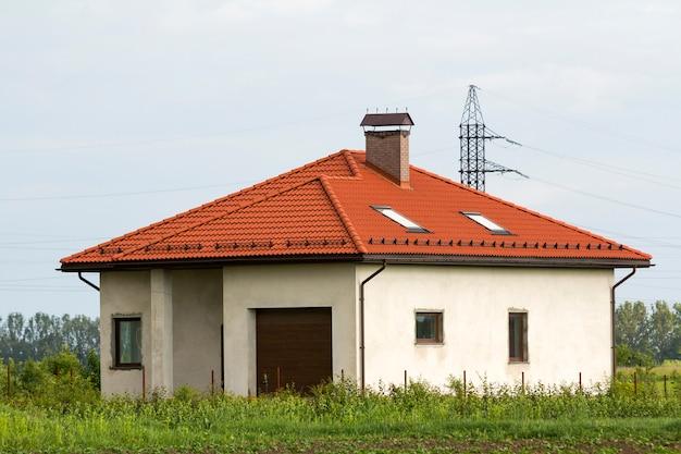 Neu gebautes, noch nicht gelebtes, einstöckiges graues haus mit ziegeldach, plastikfenstern, verputzten wänden und garage allein auf einer grünen wiese vor blauem himmel. bau- und immobilienkonzept.