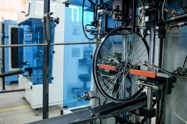 Neue aluminium-fahrradräder am fließband, speichenmontage, niemand. fahrradteile ab werk, fahrradfelgen mit naben an der maschine, moderne technik