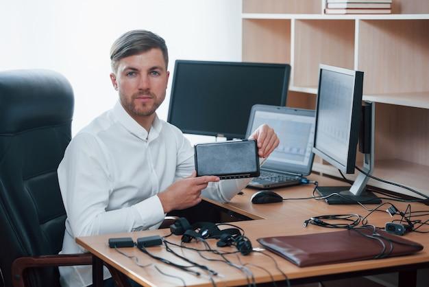 Neue ausrüstung. der polygraph-prüfer arbeitet mit seinem lügendetektor im büro