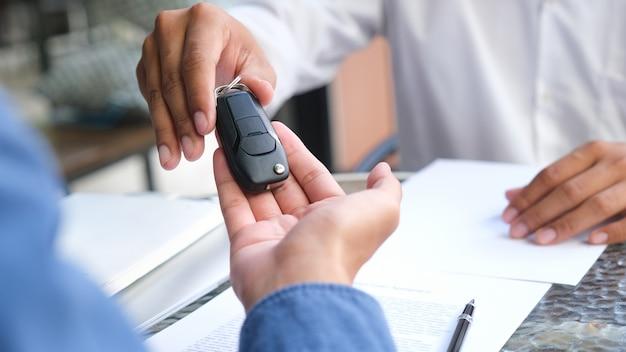 Neue autobesitzer nehmen schlüssel von männlichen verkäufern entgegen.