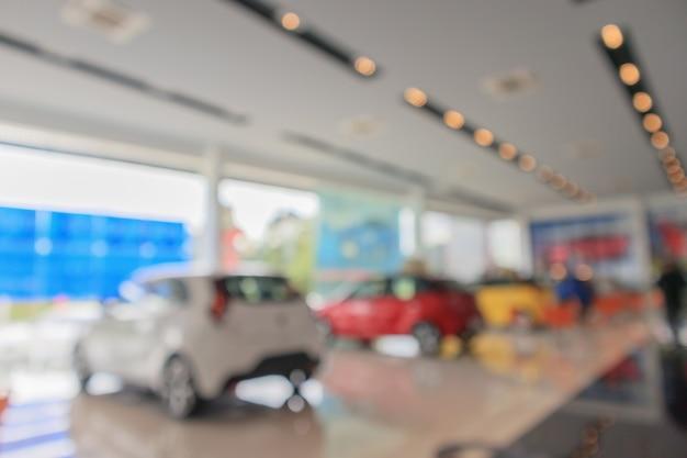 Neue autos im ausstellungsraum verwischten den unscharfen hintergrund